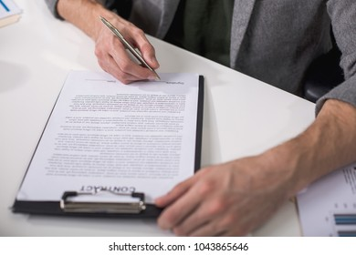 Great deal. Close up of male hands underwriting documents with pen