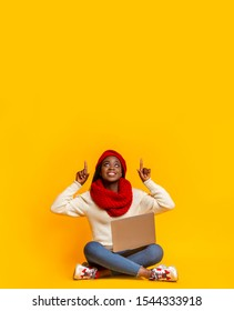 Great deal. Excited winter girl with laptop sitting on floor and pointing up at empty space, yellow studio background