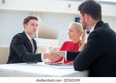 Great deal. Two successful and motivated businessmen are sitting at the table with laptops and mobile phones and shaking hands. Businesswoman looks on man