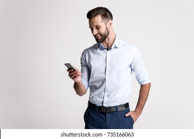 Great email! Handsome young man using his phone with smile while standing against white background.