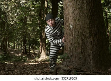The great escape. A young man in a jail prisoner suit running trough the woods.