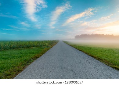 great foggy sunrise with street and fields