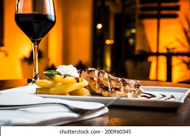 Great grilled pork fillet with red wine glass.