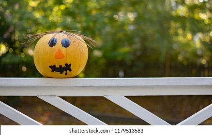 A great halloween background photo of a pumpkin with a face painted on it setting on a railing.