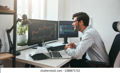 Great! Happy young businessman or trader in formalwear looking at charts on computer screen in the office and smiling