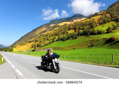 Great Highway in Austrian Alps. Among the picturesque hills at high speed motorcyclist rides