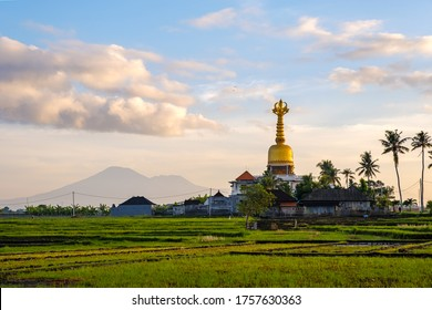 Great holy bell above the house in Seseh Tabanan, Bali. Temple with a golden Tibetan bell as a roof. Golden temple in rice fields on a background of mountains.