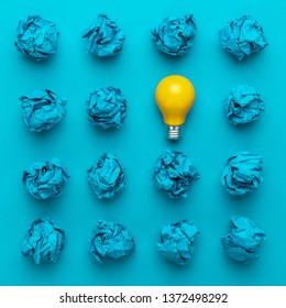 great idea concept with crumpled office paper and light bulb. top view of great business idea concept over blue background. creative solution during brainstorming session concept