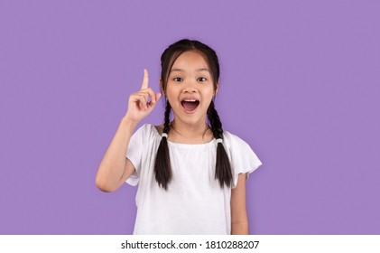 Great Idea. Little Asian Girl Pointing Finger Up Having Eureka Moment Posing On Purple Background In Studio