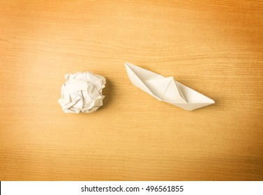 great ideas come from simple steps concept, thinking differently concept, paper boat and paper on wood background