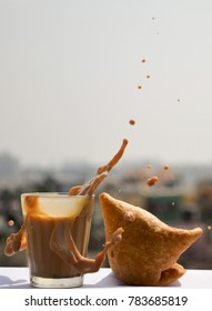 The great Indian evening snack combo of chai / tea with samosa. A splash of tea in outdoor.