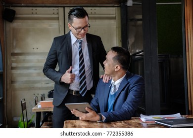Great job! excited boss encourages employee after finish project ,cheerful two young asian business man keeping arms raise celebrating success in office, business co-working teamwork concept