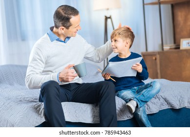 Great job. Loving young father patting his sons head, praising him for a beautifully drawn picture, while holding a cup of tea
