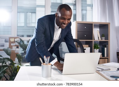 Great job. Positive satisfied young african businessman in suit is standing in office while leaning over table and typing on laptop with smile. Big window in background
