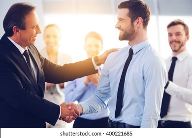 Great job! Two cheerful business men shaking hands while their colleagues applauding and smiling in the background