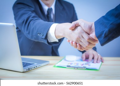 Great job,Sealing a deal,Successful business,Handshake concept.two businessman shaking hands standing at the working place,laptop and document on desk.