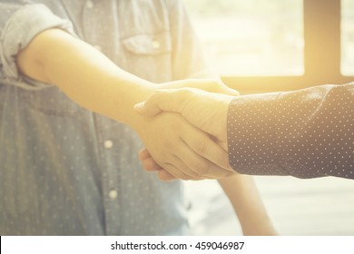 Great job,Sealing a deal,Successful business,Handshake,Business man holding hands,Good deal.two business people shaking hands standing at the working place,selective focus,Vintage tone,copy space