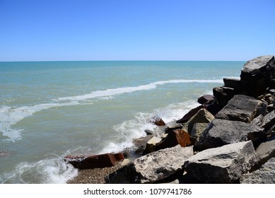 Great Lake Michigan shoreline and horizon. Blue sky and blue water with small waves crashing on a cool spring day.