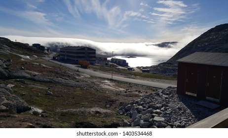 The great lake in Qaqortoq emerges from the fog.
