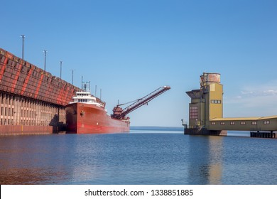 Great lakes freighter at an ore dock on Lake Superior.  Concepts could include shipping, industry, transportation, other.  Copy space in sky.