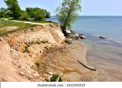 Great Lakes sand dune cliff eroding into Lake Michigan on a warm spring day with calm crystal clear waters below.