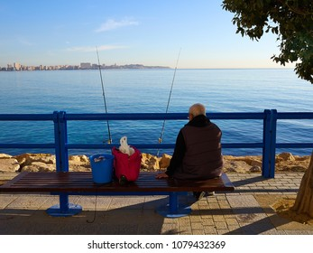 Great leisure activity - Elderly man fishing by the ocean sea