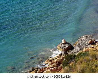 Great leisure activity - Elderly man fishing by the ocean sea in Spain