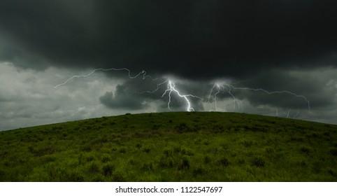 Great lightning storm behind green grass hill