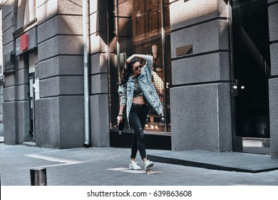 Great look. Full length of beautiful young woman in denim jacket keeping hand in hair while walking down the street