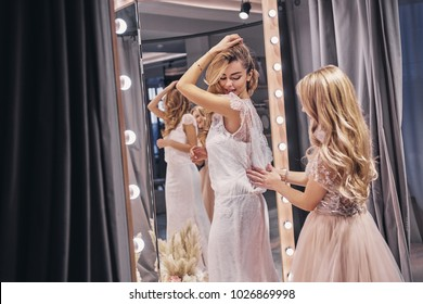 Great look! Young beautiful woman adjusting a dress on her girlfriend while standing in the fitting room