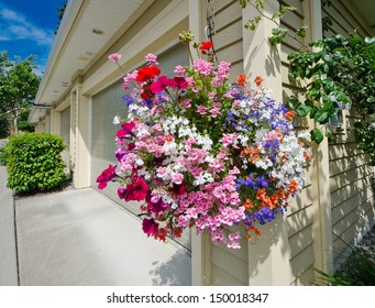 Great looking flowers basket hanging aside garage doors. Landscape design.