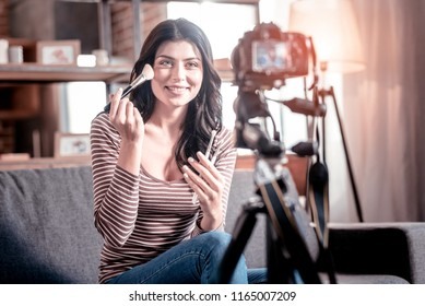 Great makeup artist. Cheerful female blogger holding brushes while making a new video for her blog