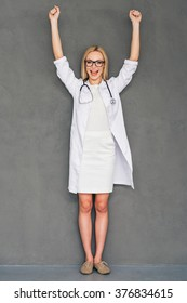 Great medical results!Beautiful young female doctor keeping hands over her head and looking at camera with smile while standing against grey background
