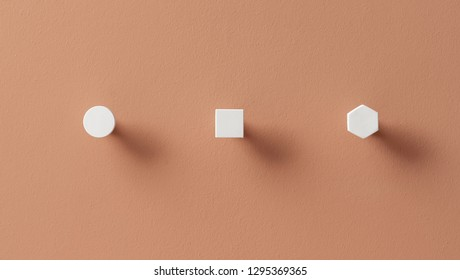 Great metal white geometric hangers on the textured orange wall indoors. They are round, square and hexagon. Closeup horizontal photo.