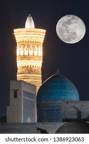 Great Minaret of the Kalon (symbol of the city) and dome of Mir-i-Arab Madrasah at night. Bukhara, Uzbekistan, Central Asia.