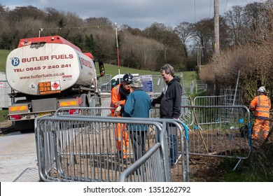 Great Missenden, Buckinghamshire/UK - March 26 2019: Construction worker on High Speed 2 (HS2) site talks to two locals about the project. Fuel lorry has just arrived. Other worker continues to work.