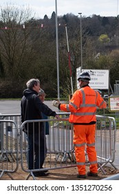 Great Missenden, Buckinghamshire/UK - March 26 2019: Construction worker discusses High Speed 2 (HS2) to locals. Worker is wearing high viz safety gear along with hard hat.