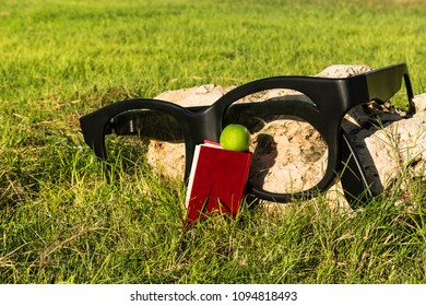 A great model of glasses for sight, a book and a green apple on the grass