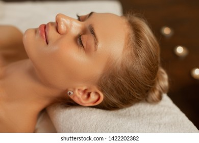 Great mood. Appealing woman with flawless skin lying on folded towel with closed eyes