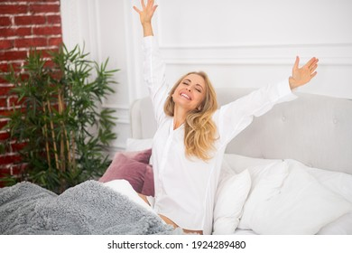 Great mood. Energetic stretching up with hands adult pretty woman in white bed in morning