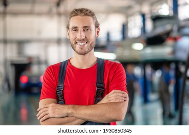 Great mood. Happy young bearded repairman in red tshirt and overalls standing with folded arms on chest in garage