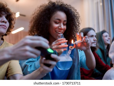 For great mood. Young afro american girl lighting marijuana in the glass bong, relaxing with friends on the sofa at home. Young people playing video games and smoking weed. Cannabis legalization
