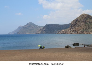 Great natural beauty at Portman in Spain near to La Manga with a view from the volcanic black sandy beach out to the islands with two figures on holiday sunbathing with parasol on stunning Summer day