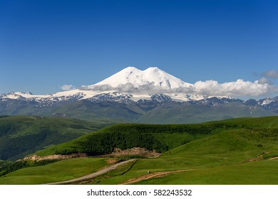 Great nature mountain landscapes. Fantastic perspective of caucasian snow inactive volcano Elbrus with green fields and road to it and clearly blue sky background. Russia