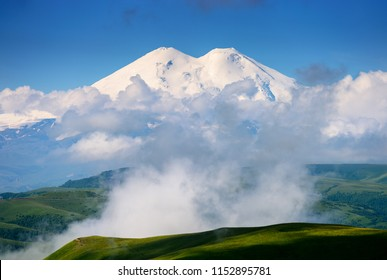 Great nature mountain range. Amazing perspective of caucasian snow mountain or volcano Elbrus with cloudy green field, blue sky background. Elbrus landscape view - highest peak of Russia and Europe