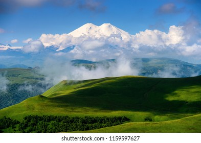 Great nature mountain range. Amazing perspective of caucasian snow mountain or volcano Elbrus with clouds, green fields, blue sky background. Elbrus landscape view - highest peak of Russia and Europe