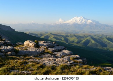 Great nature mountain range. Amazing view of caucasian snow mountain or volcano Elbrus on Bermamyt plateau at sunrise, green fields, blue sky. Elbrus landscape view - highest peak of Russia and Europe