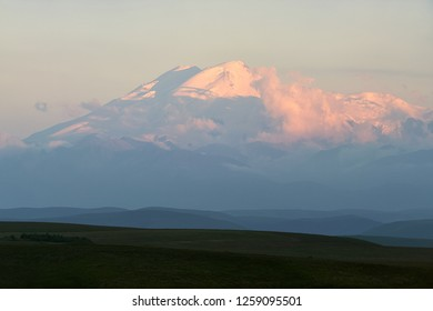Great nature mountain range. Amazing perspective of snow mountain or volcano Elbrus at sunset with clouds, green fields, blue sky background. Elbrus landscape view - highest peak of Russia and Europe