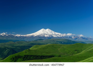 Great nature mountain range. Amazing perspective of caucasian snow mountain Elbrus with green fields, blue sky background. Elbrus landscape view - the highest peak of Russia and Europe