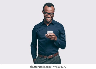 Great news from friend. Handsome young African man holding smart phone and looking at it with smile while standing against grey background